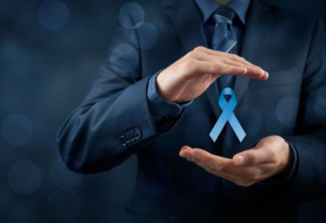Prostate cancer awareness, peace and genetic disorder awareness - man with protective and support gesture and blue ribbon. Wide banner composition and bokeh in background.