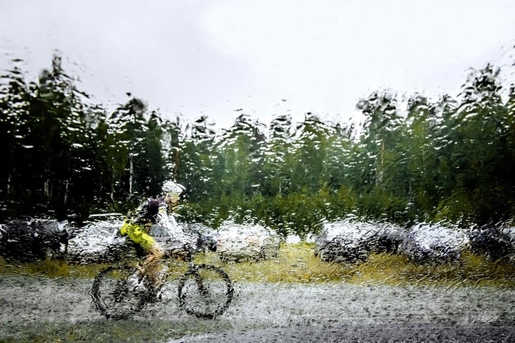 blurred silhouette behind squirt water glass of mountainbiker. autumn rainy weather